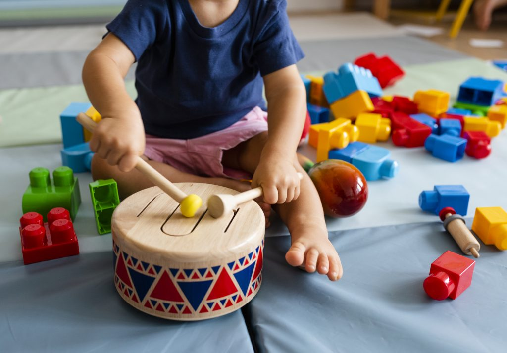 A young boy in child care in Peoria IL playing with a drum and blocks
