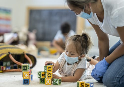 Teacher with mask talking with child with mask playing with blocks at a pre-school